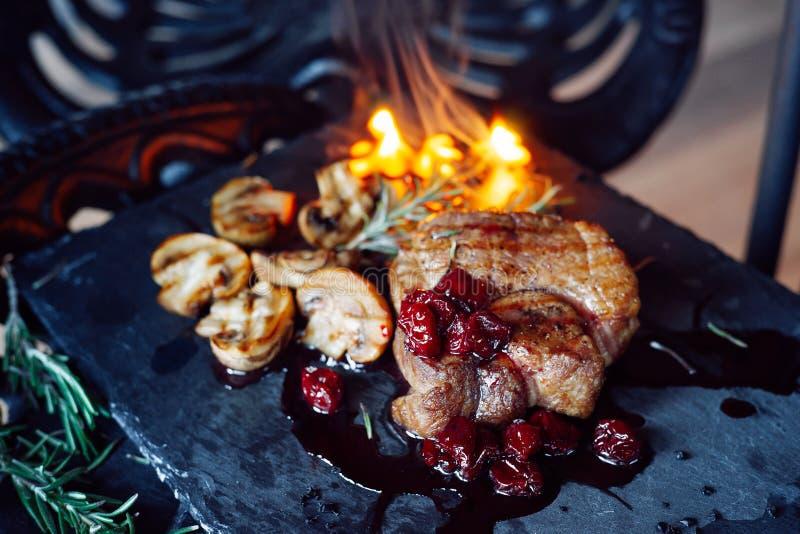 El filete del cerdo con las setas y la cereza sauce sobre fondo del vintage en el fuego foto de archivo