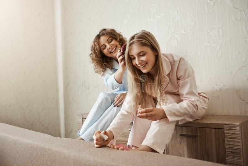 El fin de semana del gasto con la hermana es mejor que solamente Mujer rizado-cabelluda feliz encantadora en los pijamas que se p fotografía de archivo