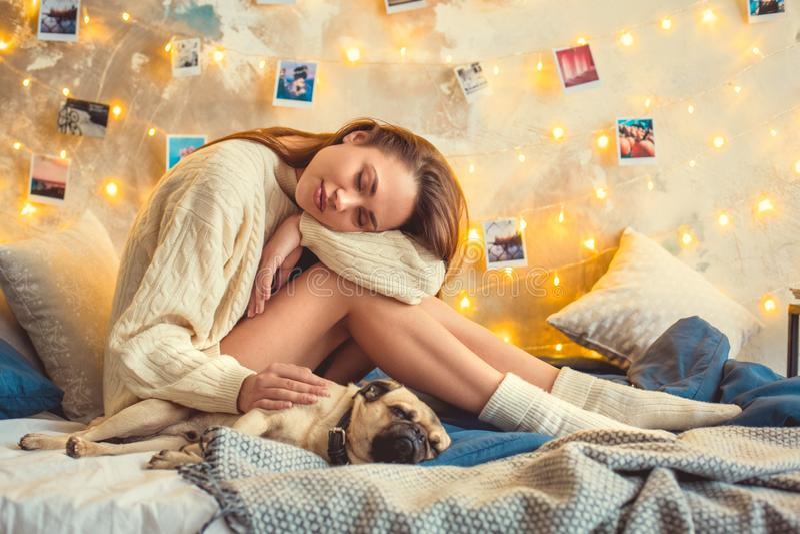 El fin de semana de la mujer joven en casa adornó el dormitorio con el perro que dormía en rodillas imágenes de archivo libres de regalías