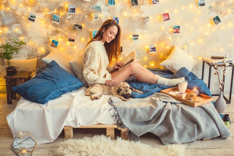 El fin de semana de la mujer joven en casa adornó el dormitorio que frotaba ligeramente el libro de lectura del perro imagenes de archivo