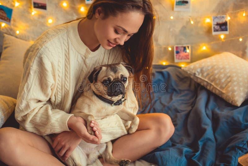 El fin de semana de la mujer joven en casa adornó el dormitorio que sostenía la pata del perro imágenes de archivo libres de regalías