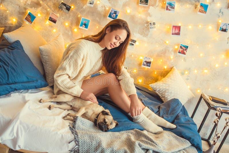 El fin de semana de la mujer joven en casa adornó el perro conmovedor del dormitorio fotos de archivo