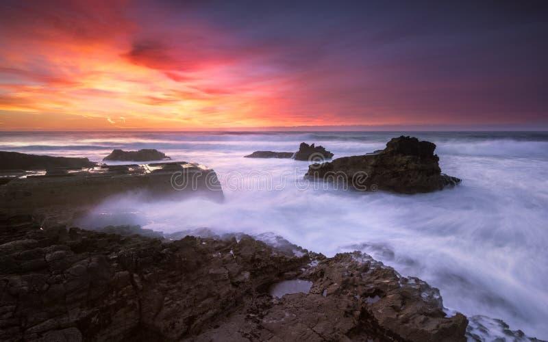 El final de un día colorido en una playa aislada, comtemplando la puesta del sol fotografía de archivo