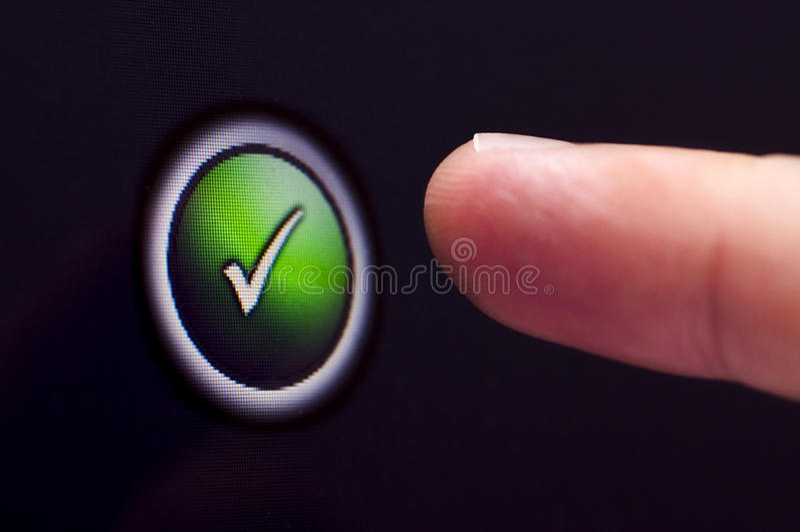 El finger presiona el botón de la señal del verde de la pantalla táctil foto de archivo