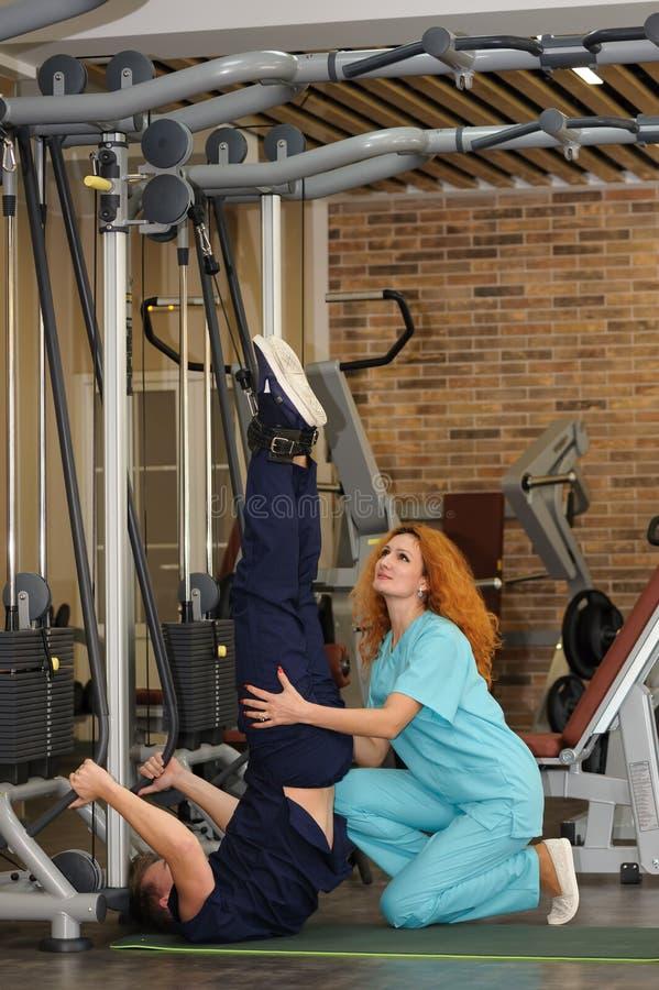 El fisioterapeuta ayuda al paciente a rehabilitar imagen de archivo