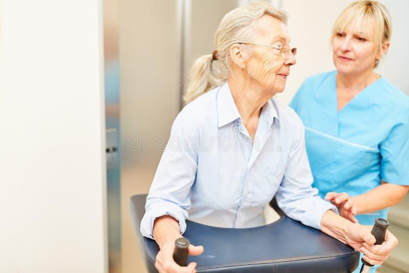 El fisioterapeuta ayuda a la mujer con rollator foto de archivo libre de regalías