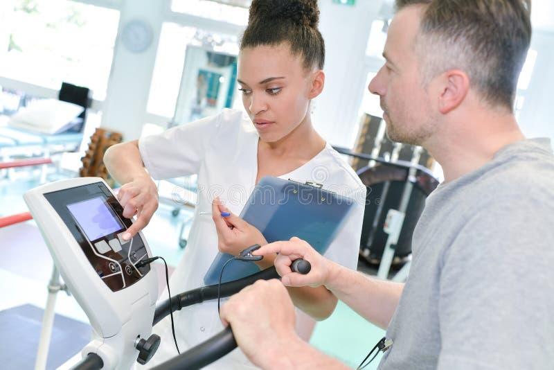 El fisioterapeuta del doctor ayuda al paciente a restaurar el movimiento imagenes de archivo