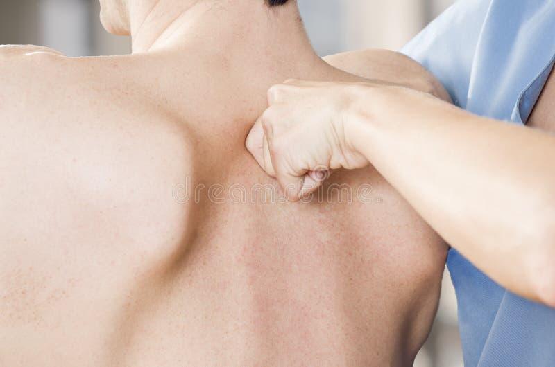 El fisioterapeuta está probando alto dorsal en una clínica fotografía de archivo libre de regalías