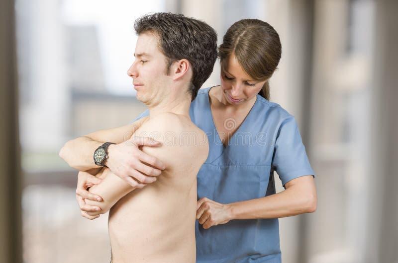 El fisioterapeuta está probando dorsal bajo en una clínica foto de archivo
