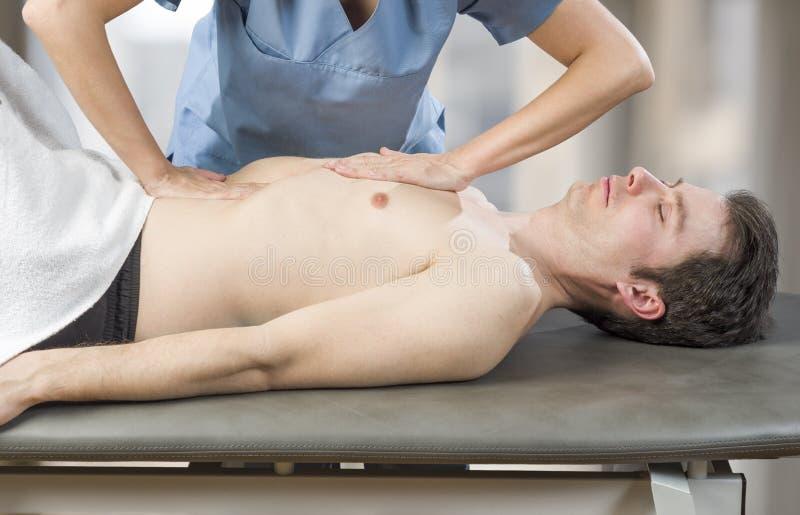 El fisioterapeuta, quiropráctico está haciendo una activación del diafragma Masaje a un paciente del hombre osteopathy fotos de archivo