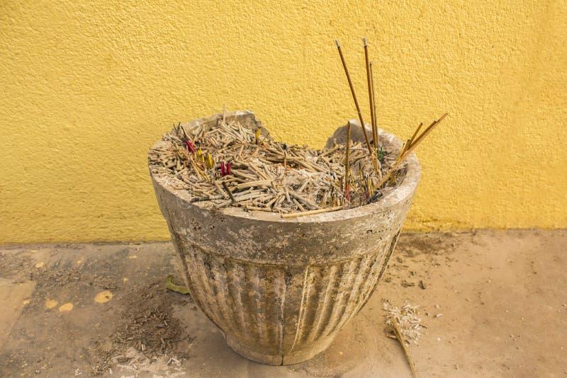 El florero viejo para el incienso ardiente pega soportes del primer en el piso contra la perspectiva de la pared amarilla imágenes de archivo libres de regalías