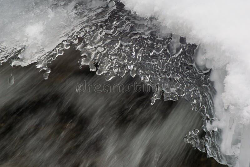 El fluir frío del agua de la corriente de los cristales de hielo del invierno fotos de archivo libres de regalías