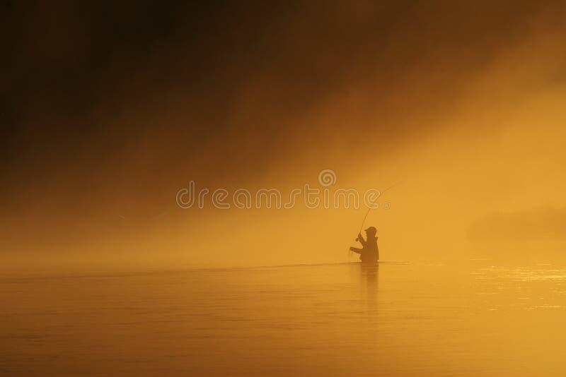 El Fly-fishing en la puesta del sol fotos de archivo