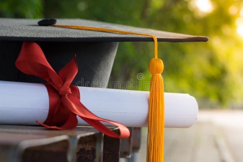 El foco ascendente cercano del graduado de la universidad sostiene el certificado del grado y el casquillo de la graduación celeb imagen de archivo libre de regalías