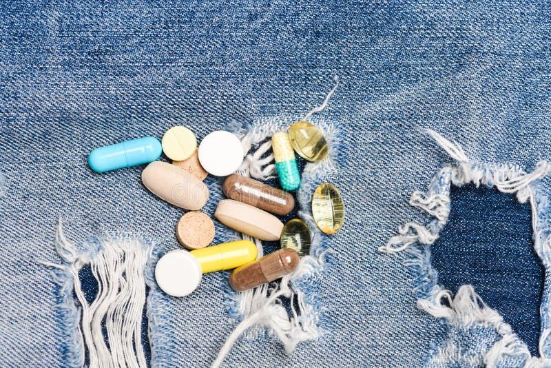 El foco está en la jeringuilla Concepto de la medicina y del tratamiento Drogas en fondo del dril de algodón Conjunto de píldoras imagenes de archivo