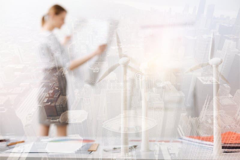 El foco selectivo de los molinos de viento modela en la tabla de un ingeniero profesional imágenes de archivo libres de regalías