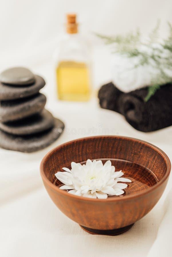 el foco selectivo del arreglo de los accesorios del tratamiento del balneario y el crisantemo florecen en cuenco de madera imagen de archivo