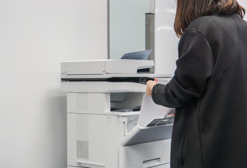 El foco selectivo en la empresaria en chaqueta negra puso la hoja de papel en la bandeja de la impresora de oficina para los docu foto de archivo libre de regalías