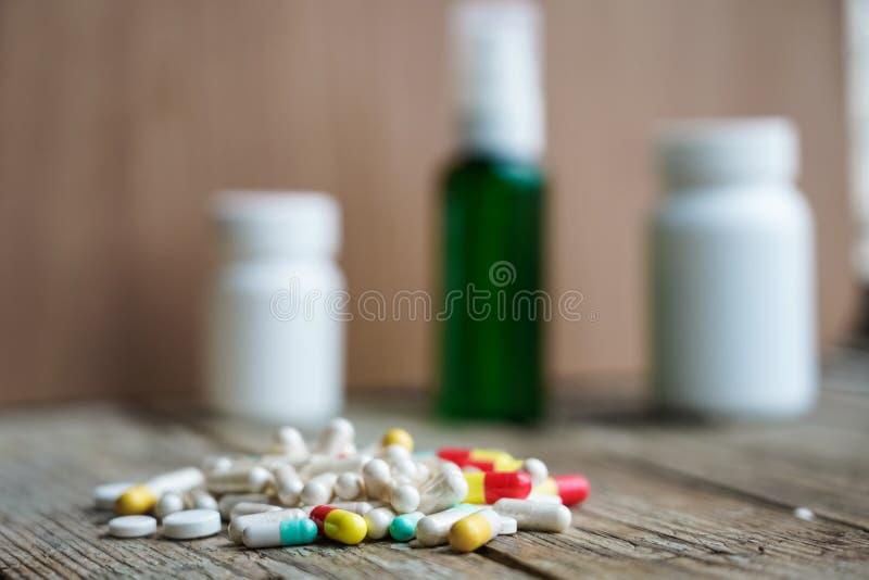 El foco selectivo en píldora se separó en fondo de madera concepto global de la atención sanitaria Industria farmacéutica imagenes de archivo