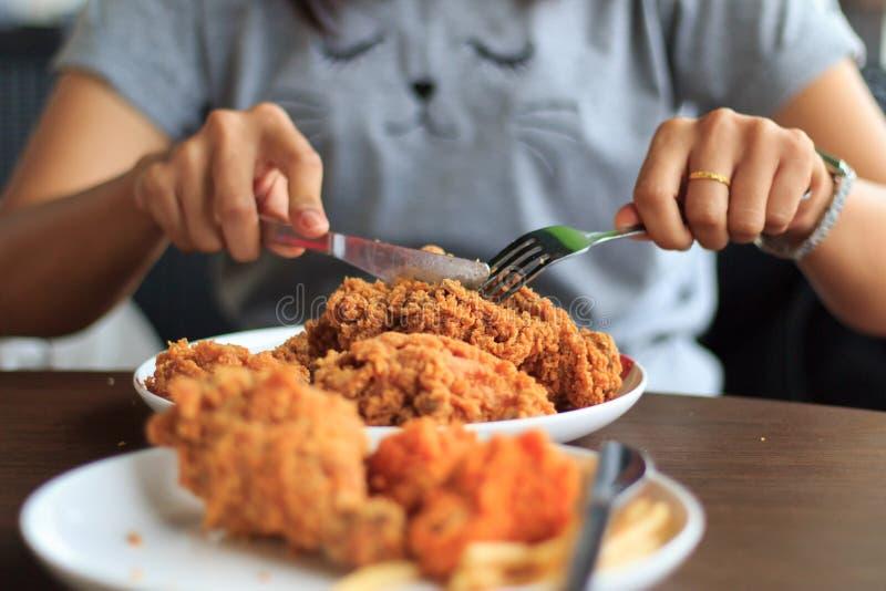 El foco selecto del pollo frito del corte de la mujer joven, almuerzo del pollo frito, mujer del primer da el pollo frito del cor imagen de archivo libre de regalías