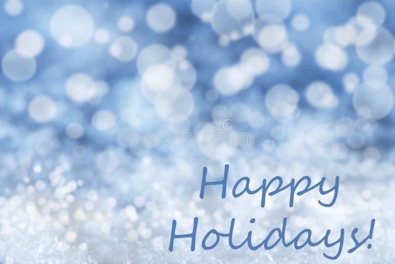 El fondo azul de la Navidad de Bokeh, nieve, manda un SMS buenas fiestas fotografía de archivo