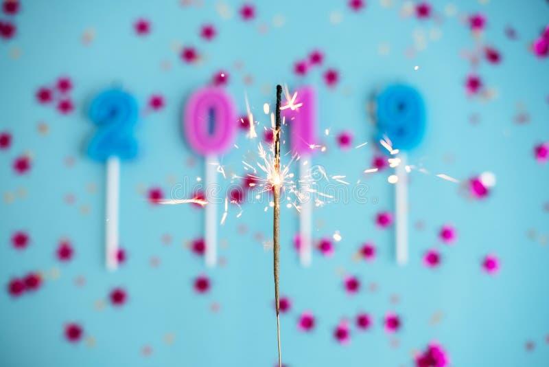 El fondo azul del Año Nuevo y de la Navidad del día de fiesta festivo con el confeti, estrellas, bengalas, mira al trasluz 2019 C fotografía de archivo libre de regalías