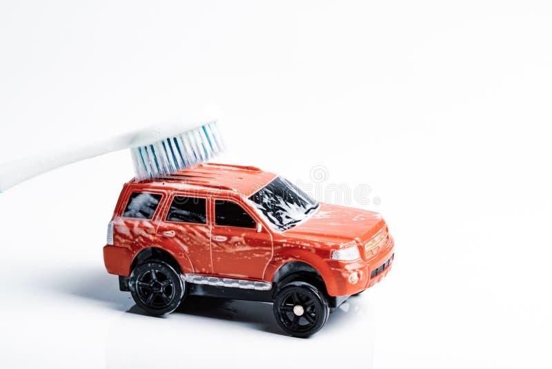 El fondo blanco en él es un coche rojo del juguete que lava un cepillo de dientes fotos de archivo libres de regalías