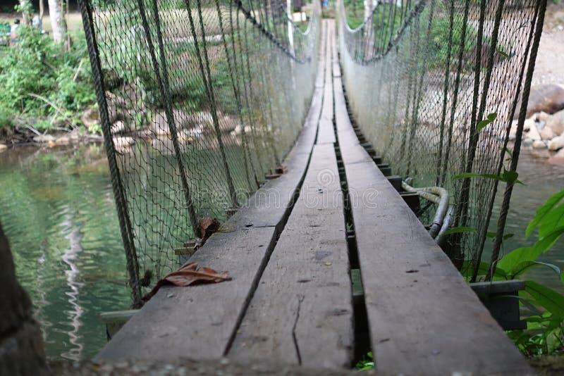 El fondo borroso de las sujeciones de un puente de madera con la honda de la cuerda de alambre utilizó cruces la corriente fotos de archivo libres de regalías