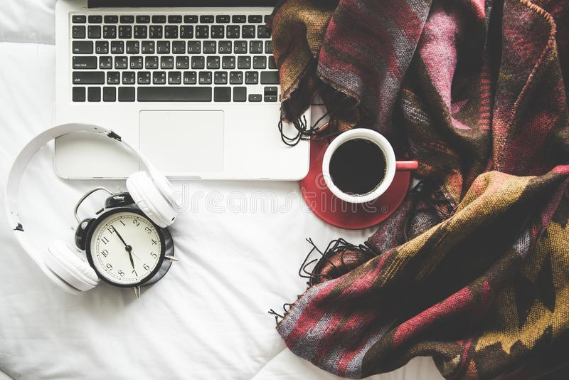 El fondo casero del invierno acogedor, taza de café caliente con la melcocha, calienta el suéter hecho punto en el fondo blanco d fotos de archivo