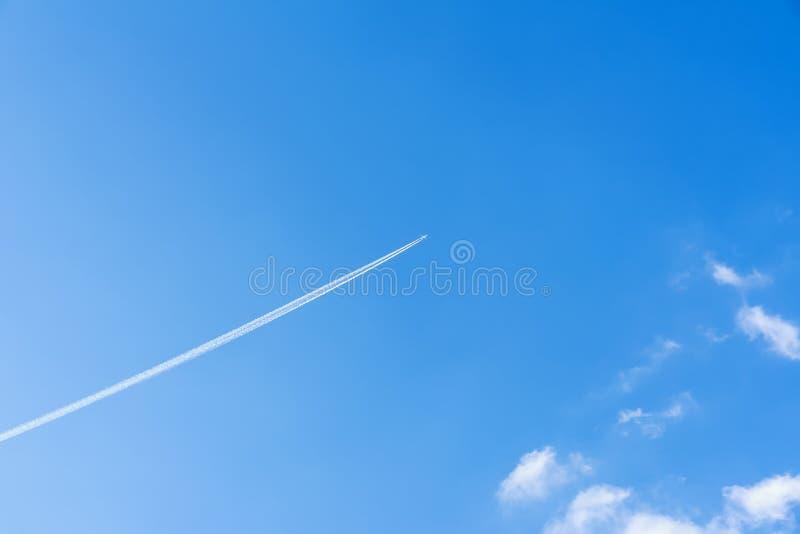 El fondo claro brillante de cielo azul con el rastro diagonal del avión de reacción, pista, rastro del aeroplano, rastros de cond foto de archivo