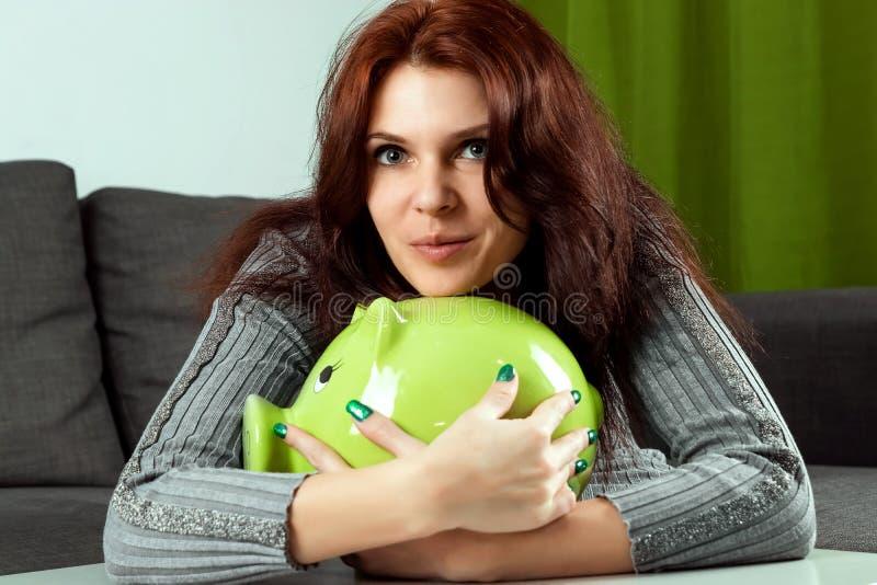 El fondo creativo, una muchacha hermosa abraza una hucha bajo la forma de cerdo verde El concepto de dinero de ahorro, ahorros, c fotos de archivo