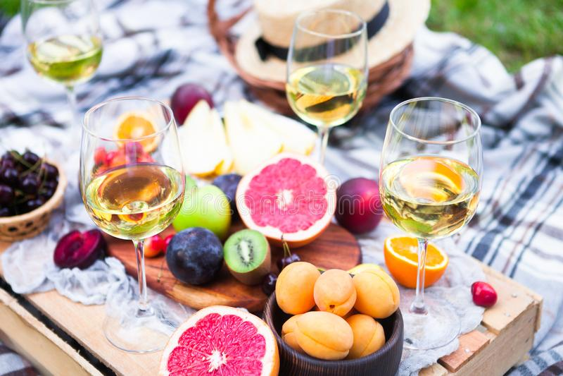 El fondo de la comida campestre con el vino blanco y el verano da fruto en gra verde fotografía de archivo libre de regalías