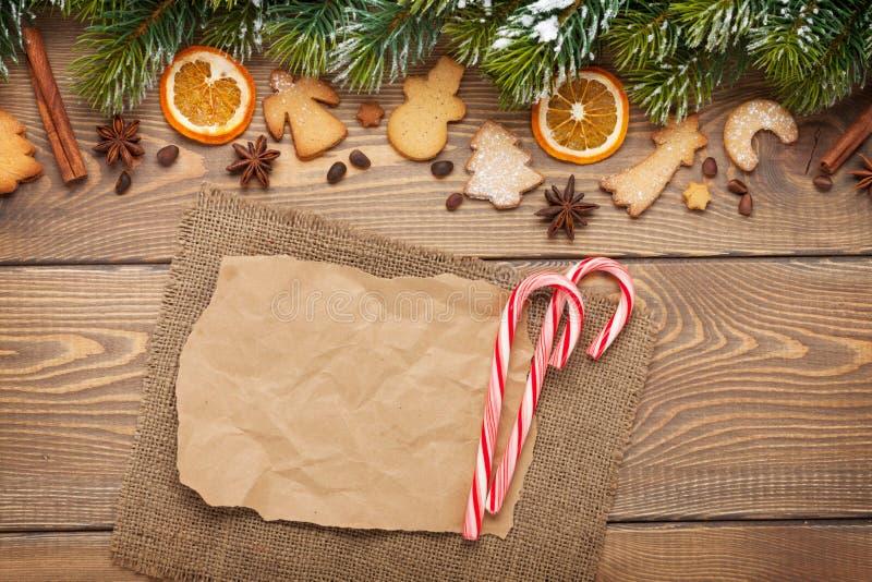 El fondo de la Navidad con el árbol de abeto de la nieve, especias, pan de jengibre arrulla imagenes de archivo