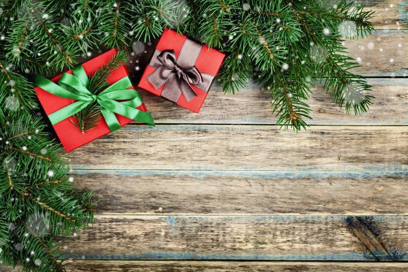 El fondo de la Navidad con la caja de regalo y el abeto ramifican en el tablero rústico de madera, efecto festivo de la nieve, ma fotografía de archivo
