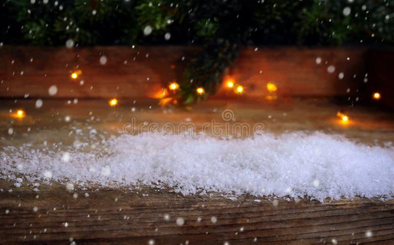 El fondo de la Navidad, nieve, luces, abeto ramifica en la madera foto de archivo