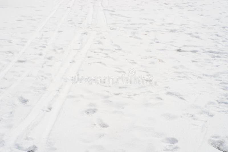 El fondo de la nieve con el esquí remonta impresiones del pie del ADN fotografía de archivo
