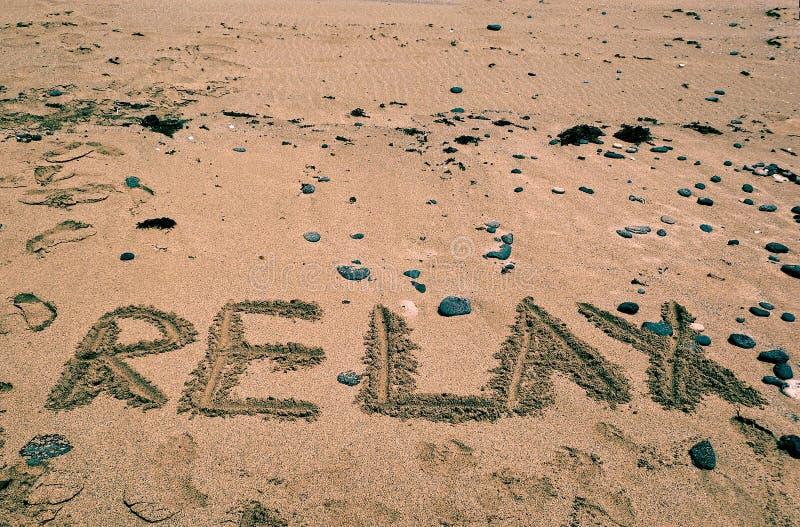 El fondo de los días de fiesta con RELAJA la palabra escrita en la playa arenosa Fondo de los días de fiesta Verano En relaje el  foto de archivo libre de regalías