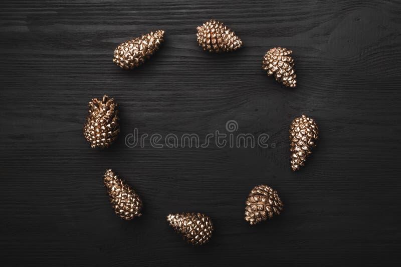 El fondo de madera negro con la textura destacó con los conos de oro en la forma de un círculo en él imágenes de archivo libres de regalías