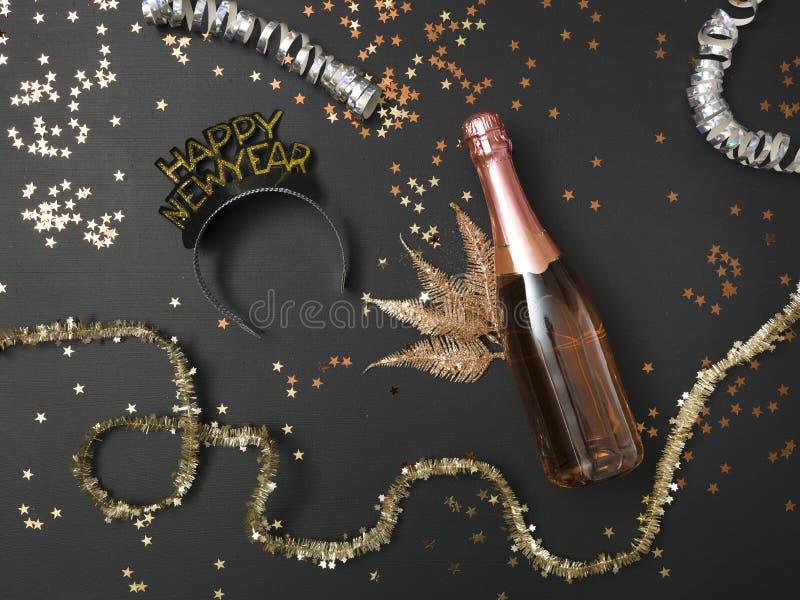 El fondo de nuevo Yearcon una botella de champán y de los diversos utensilios del Año Nuevo encendido imagen de archivo