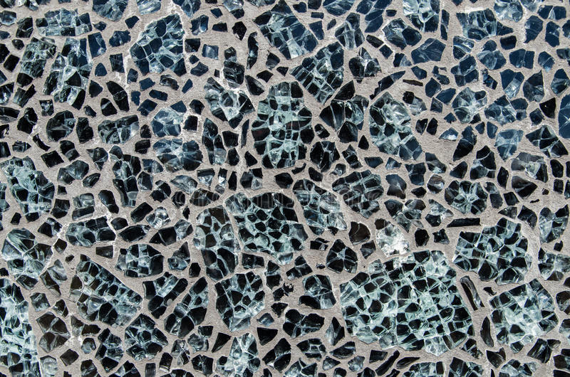 El fondo de piedras negras pulidas fijó en el cemento o el hormigón foto de archivo