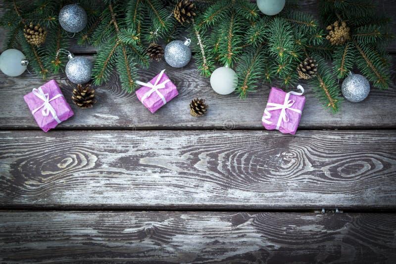 El fondo del día de fiesta de la Navidad con las cajas de regalos con el abeto ramifica, los conos del pino, bolas de la Navidad  fotografía de archivo