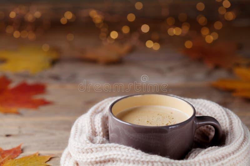 El fondo del otoño de la taza de cacao o del café en bufanda hecha punto en la tabla de madera adornada con caída se va Bebida ca imagen de archivo libre de regalías