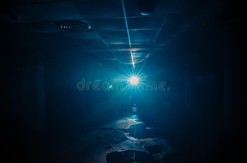 El fondo del sitio azul de neón de luz laser con humo que remolina brilla a través de un cuarto vacío fotos de archivo