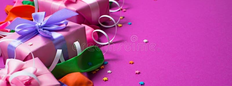 El fondo festivo de la bandera del plano colorido material púrpura de la opinión superior del regalo de las cajas del confeti tre foto de archivo