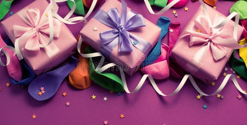 El fondo festivo de la bandera del plano colorido material púrpura de la opinión superior del regalo de las cajas del confeti tre foto de archivo libre de regalías