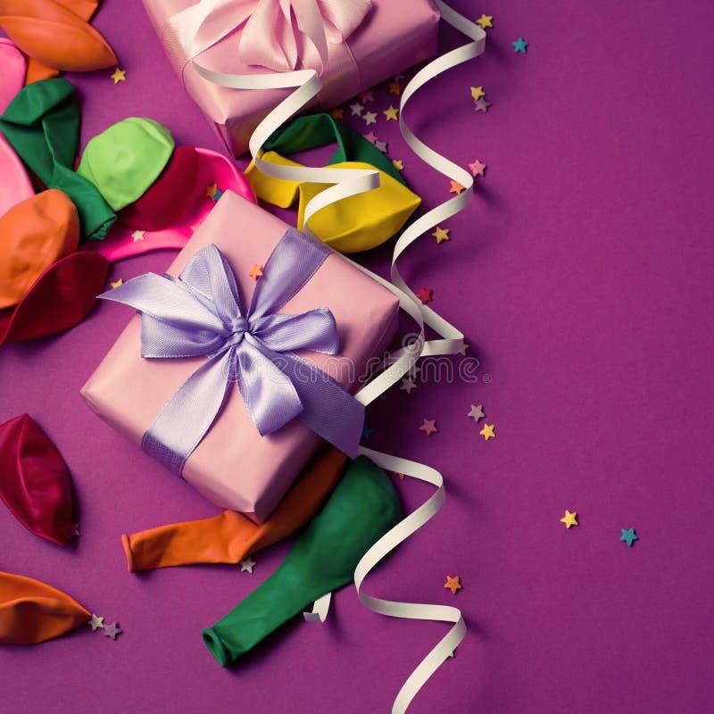 El fondo festivo del confeti colorido material púrpura dos de las flámulas de los globos encajona el espacio de la copia de la en imágenes de archivo libres de regalías