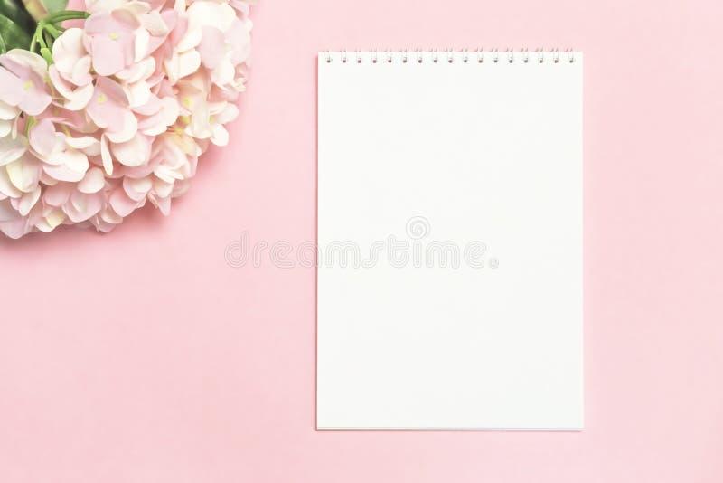 El fondo festivo en colores en colores pastel ramifica de hortensia artificial delicada en un fondo rosado con un cuaderno para e fotos de archivo