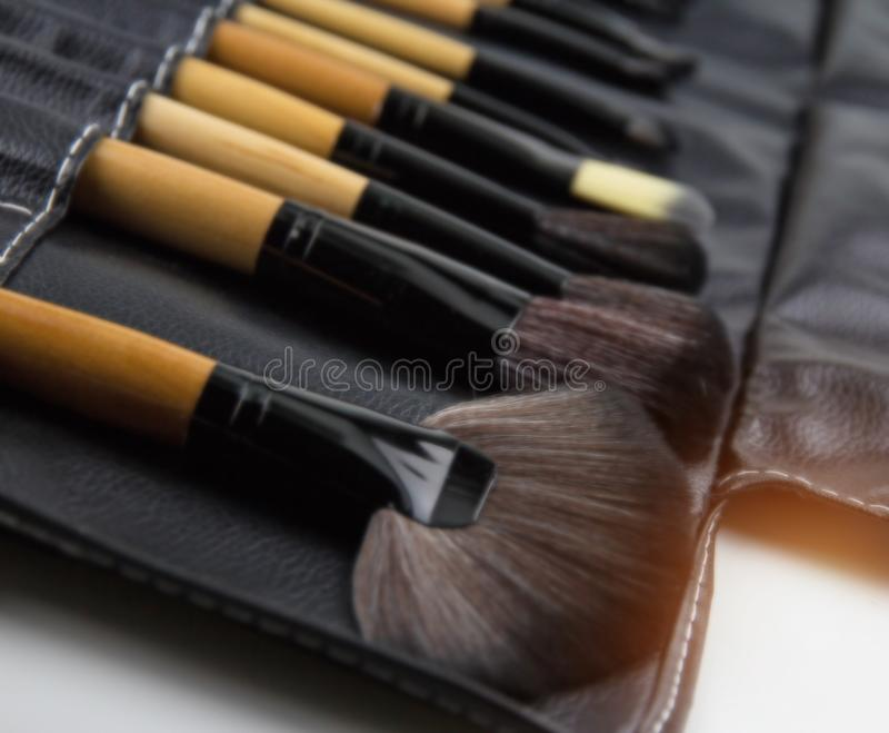 El fondo ligero borroso del diseño del sistema de cepillo cosmético puesto en caja de cuero negra, para compone, sistema de cepil foto de archivo libre de regalías