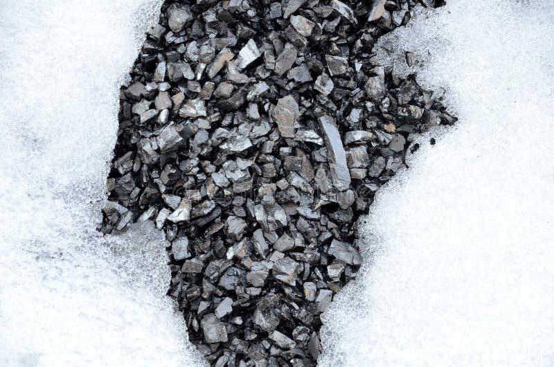 El fondo que consiste en dos porciones de la nieve y de una parte de antracita del carbón bajo la forma de remiendos deshelados fotografía de archivo libre de regalías