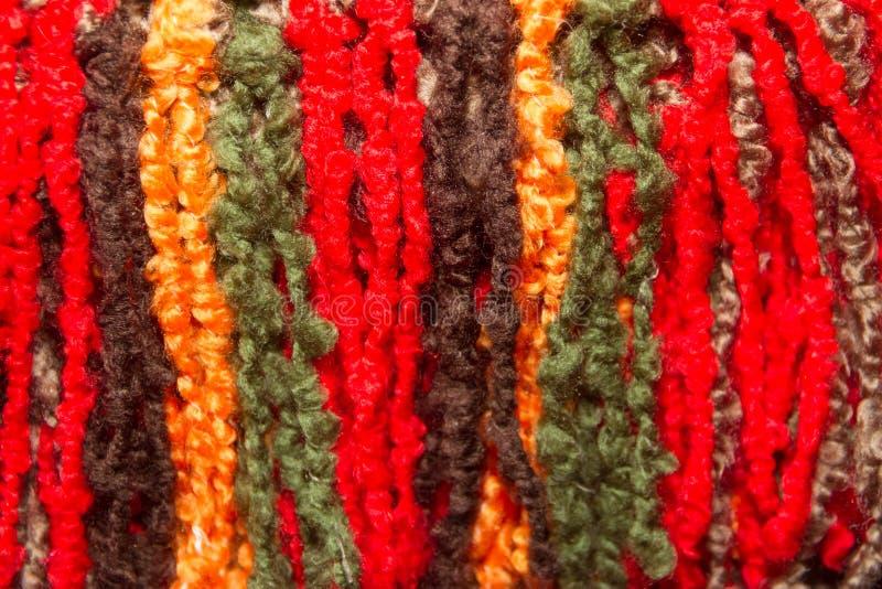 El fondo texturizado con las franjas hechas con lanas multicoloras rosca foto de archivo